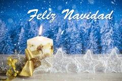 与蜡烛,金黄弓,银色星的圣诞节装饰,与在西班牙` Feliz Navidad `的文本在蓝色森林背景中 免版税库存图片
