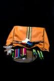 与蜡笔和刷子的橙色大袋子 库存照片