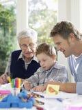与蜡笔的男孩图画有父亲和祖父的 免版税库存照片
