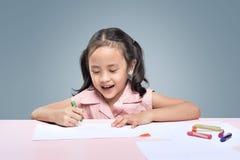 与蜡笔的美丽的亚洲小女孩图画 免版税库存照片