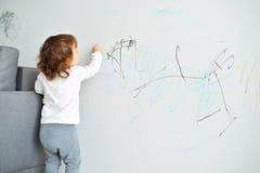 与蜡笔颜色的卷曲逗人喜爱的小的女婴图画在墙壁上 孩子工作  免版税库存照片