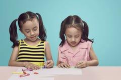 与蜡笔画的创造性的两个亚洲人孩子在书桌上 库存照片