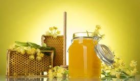 与蜡蜂窝和蜂蜜的木制框架在瓶子,在黄色背景 免版税库存照片