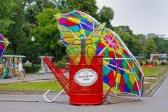 与蝴蝶的红色喷壶在伞下当节日`莫斯科夏天`的艺术设施在Bolotnaya广场在莫斯科 图库摄影