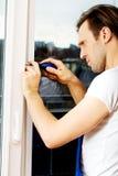 与螺丝刀的年轻杂物工修理窗口 库存图片