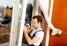 与螺丝刀的年轻杂物工修理窗口 免版税库存照片