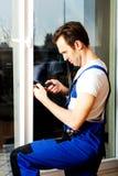 与螺丝刀的年轻杂物工修理窗口 免版税库存图片