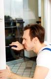 与螺丝刀的年轻杂物工修理窗口 图库摄影