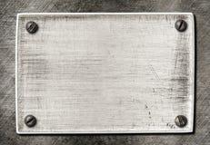 与螺丝的老被抓的金属纹理 免版税库存图片