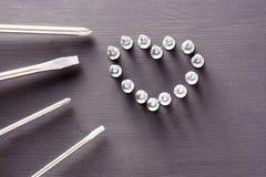 与螺丝的螺丝刀集合被计划以在灰色木桌上的心脏的形式 父亲` s天,人, DIY的概念 免版税库存图片