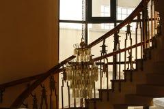 与螺旋形楼梯的中产阶级的房子内部与富有的木扶手栏杆和一盏富有的华丽枝形吊灯 免版税库存图片