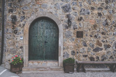 与螺栓的老绿色木门有城堡墙壁纹理的 库存照片
