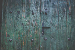 与螺栓的老绿色木门 免版税库存图片