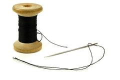 与螺纹的木卷和缝合的一根针在白色背景 库存照片