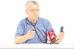 与血压计的老人测量的血压 免版税库存照片