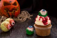 与血液妖怪眼睛的万圣夜杯形蛋糕 库存图片