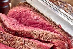 与血液的油煎的肉与猎刀 井做的牛排特写镜头 土气样式 免版税库存照片