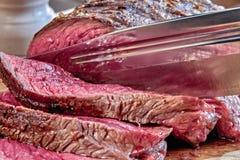 与血液的油煎的肉用猎刀切 井做的牛排特写镜头 土气样式 库存图片