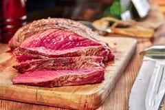 与血液的烤肉 新鲜的热的牛排和刀子特写镜头 木背景 选择聚焦 库存图片