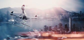 与行动照相机飞行天空的照片白色表面无光泽的普通设计遥控空气寄生虫在城市下 现代megapolis 免版税库存图片
