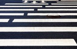 与行动的白色标号线和方向的斑马线 库存图片