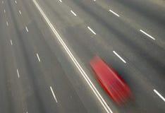 与行动迷离的红色汽车 库存图片