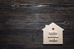 与行情的家庭标志和心脏在木背景塑造与 库存照片