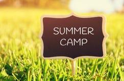 与行情的木黑板标志:夏令营 库存照片