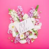 与行情`的纸牌我的爱`和白色毛茛属、snapdragon、郁金香和小苍兰在桃红色背景 平的位置 顶视图 库存照片