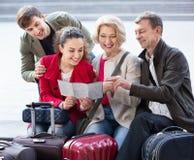 与行李检查在地图的四口之家方向 库存图片