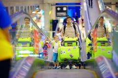 与行李的愉快的家庭在传动机在机场,准备旅行 库存照片