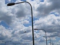 与街灯和多云天空一起的飞行平面飞机旅行 库存照片