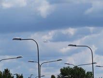 与街灯和多云天空一起的飞行平面飞机旅行 免版税库存图片