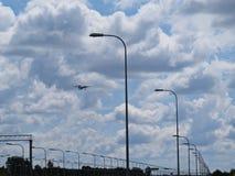 与街灯和多云天空一起的飞行平面飞机旅行 库存图片