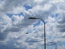 与街灯和多云天空一起的飞行平面飞机旅行 免版税库存照片
