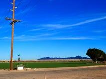 与街道和绿色领域的电塔 免版税库存图片