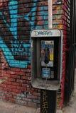 与街道画公用电话立场的街道视图 库存照片