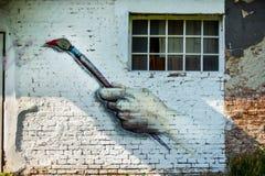 与街道画油漆的抽象老墙壁砖和窗口在晴天在城市停放 免版税图库摄影