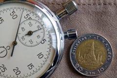 与衡量单位的泰国硬币10泰铢和秒表在老米黄牛仔裤背景-企业背景 免版税库存照片