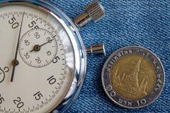 与衡量单位的泰国硬币10泰铢和秒表在老蓝色牛仔布背景-企业背景 免版税库存图片