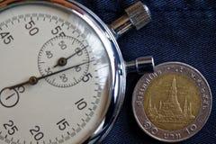 与衡量单位的泰国硬币10泰铢和秒表在老被佩带的深蓝牛仔裤背景-企业背景 库存图片