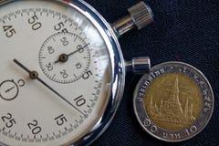 与衡量单位的泰国硬币10泰铢和秒表在老被佩带的黑牛仔裤背景-企业背景 免版税库存图片