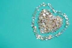 与衣服饰物之小金属片和小珠的心脏的蓝色背景 免版税库存照片