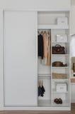 与衣裳和辅助部件的白色壁橱 免版税库存图片