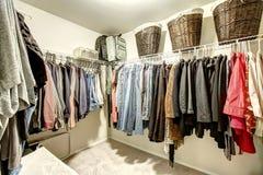 与衣裳的可容人走进去的大壁橱 免版税库存图片