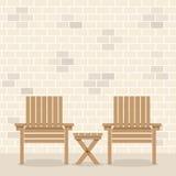 与表的木庭院椅子在砖墙前面 库存图片