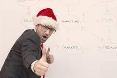 与表示圣诞老人的帽子的商人显示他的赞许的满意 库存图片