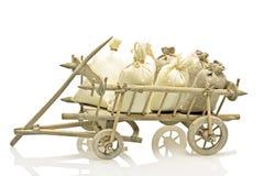 与袋子的古板的木手车秸杆和土豆 库存图片