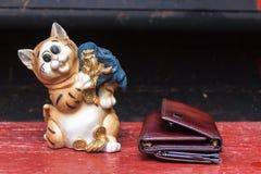 与袋子的老虎有很多金钱和钱包在木地板上 库存照片