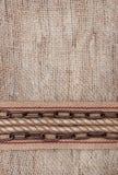 与袋装的丝带、金属链子和绳索的粗麻布背景 图库摄影